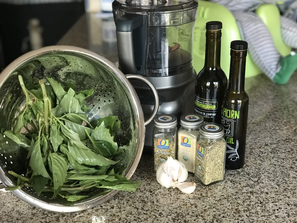 Herbs, dry seasonings, garlic, and olive oil on a countertop
