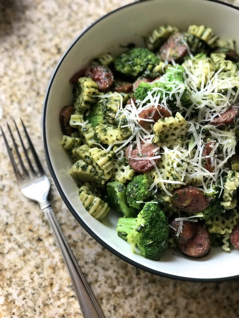 An overhead shot of a bowl of pasta with broccoli and sausages