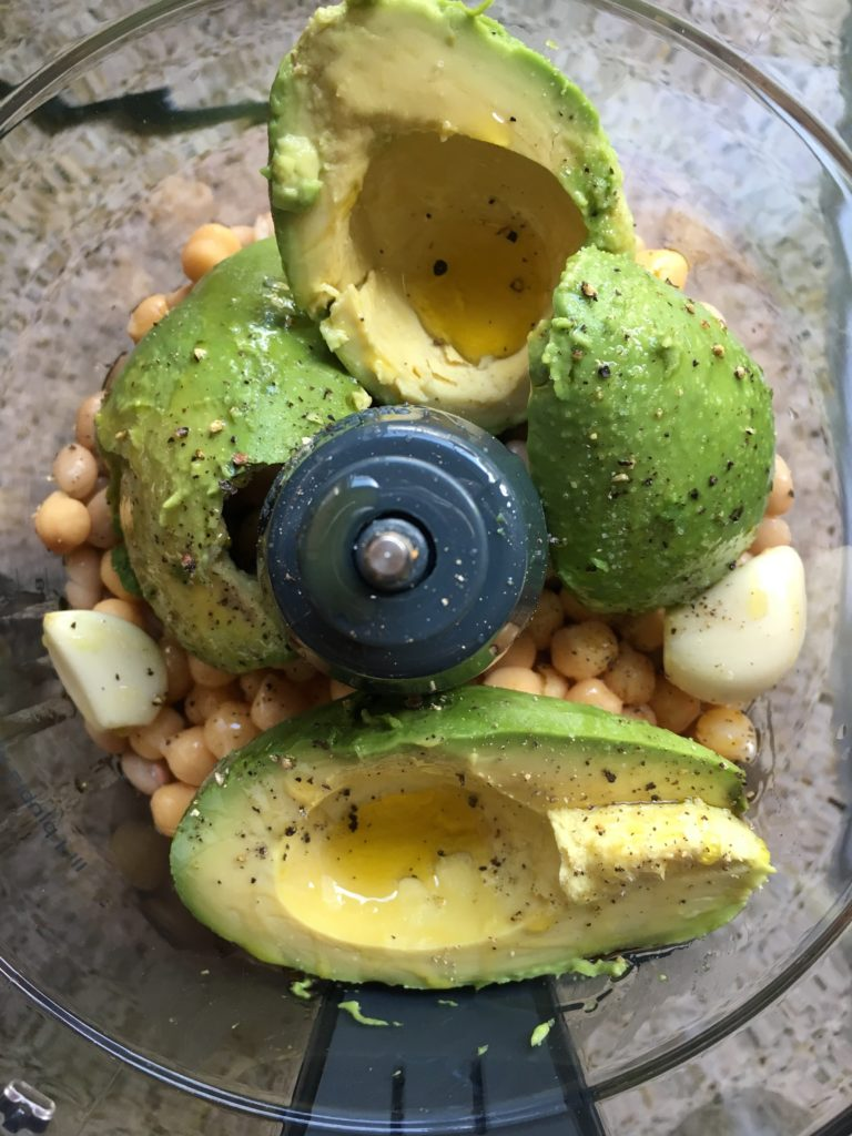 Overhead shot of avocados, garlic, chickpeas, and spices in a food processor
