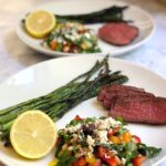 Shot of two plates of grilled sirloin with mediterranean farro salad