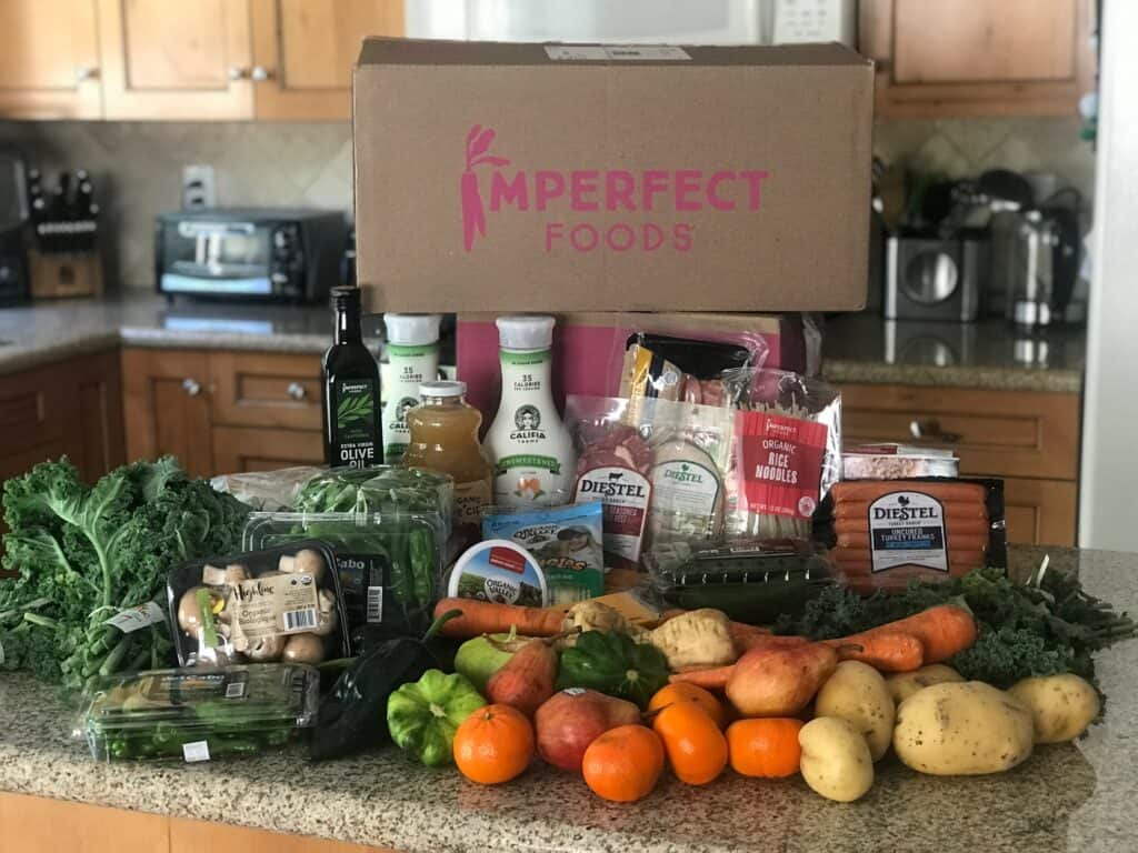 Shot of Imperfect Foods delivery box with grocery items displayed in front