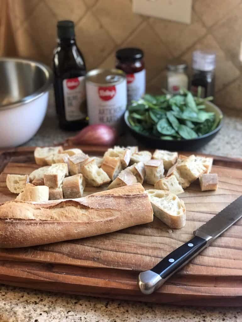 Shot of cubed bread on a cutting board in front of bottles of oil and spices