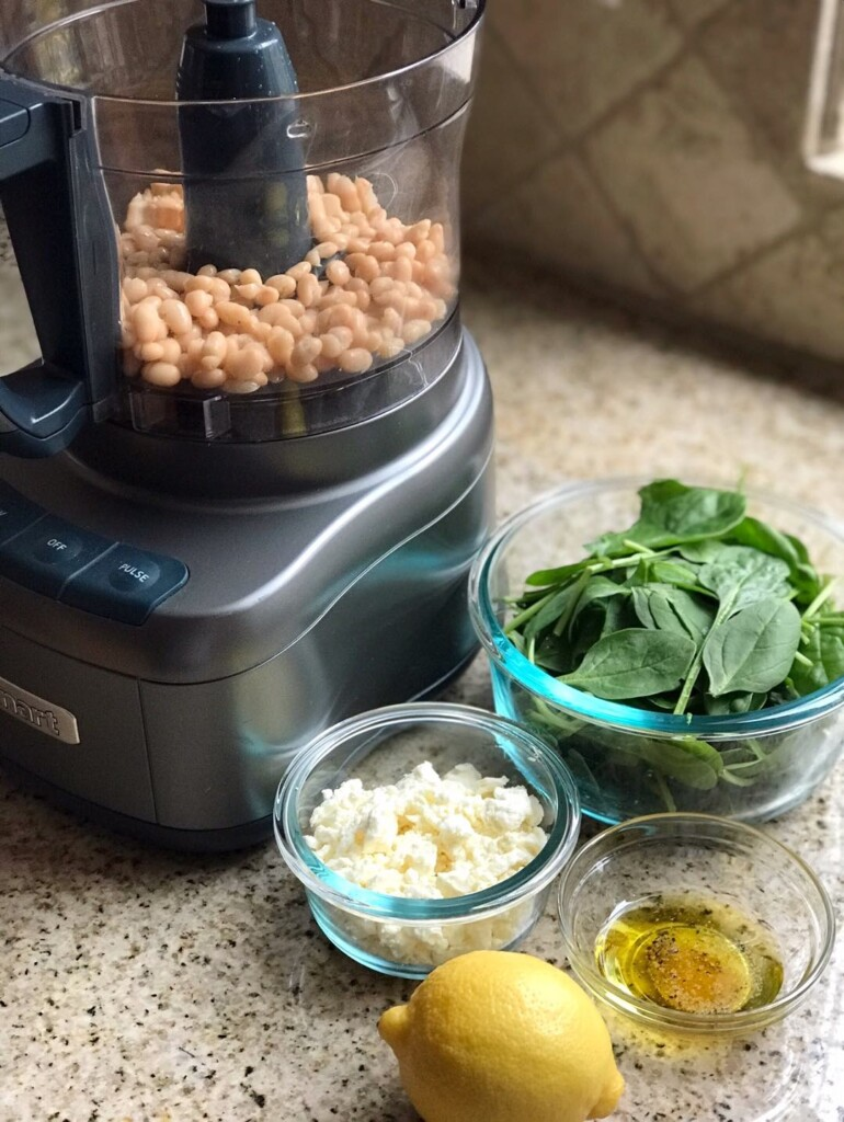 Side view of dip ingredients next to a food processor