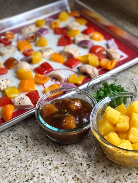 Side-view of sheet pan pineapple chicken next to bowls of sauce, scallions, and pineapple pieces