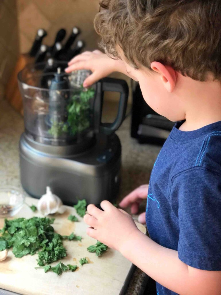 Boy placing chimichurri ingredients into a food processor