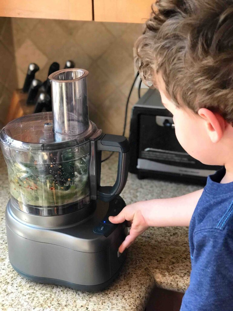 Boy blending chimichurri ingredients in a food processor